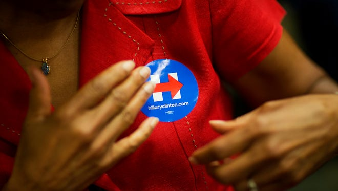 A Hillary Clinton supporter puts on a sticker at one of Clinton's campaign stops in Santee, S.C, on June 17, 2015.