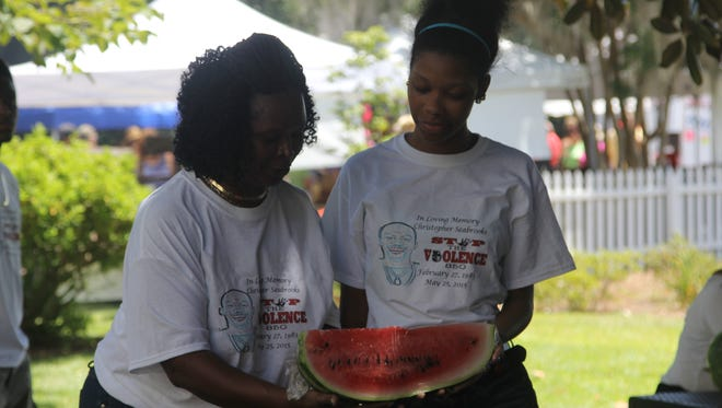 Jefferson County locals Christie Seabrooks and her daughter Kadijeah Hayes eye an ice cold slice of watermelon Saturday.