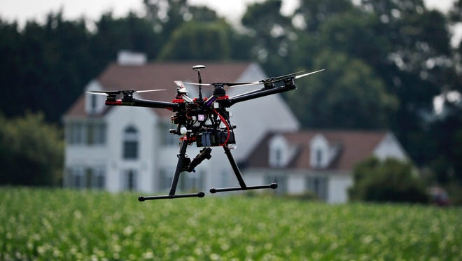 In this June 11, 2015, photo, a hexacopter drone is flown by Intelligent UAS, during a drone demonstration at a farm and winery on potential use for board members of the National Corn Growers in Cordova, Md. The small, relatively inexpensive unmanned aerial vehicles could replace humans in a variety of ways around large farms, transmitting detailed information about crops, directing farmers to problem spots and cutting down on the amount of water and chemicals used. (AP Photo/Alex Brandon)