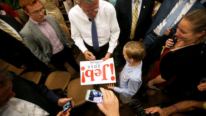 Republican Presidential hopeful Jeb Bush autographs a sign for a young supporter after speaking at the Augustus B. Turnbull III Florida State Conference Center on Monday.