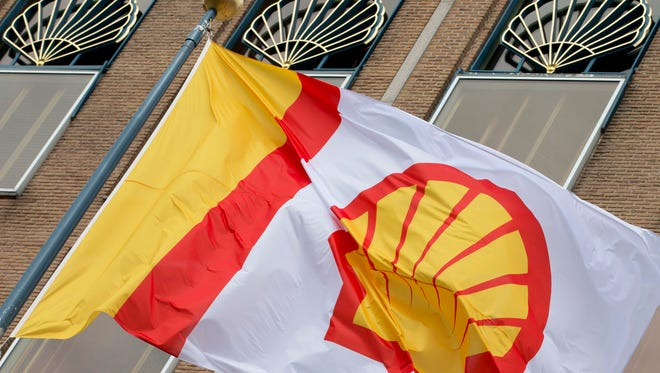 FILE - In this Monday, April 7, 2014 file photo, a flag bearing the company logo of Royal Dutch Shell, flies outside the head office in The Hague, Netherlands. Royal Dutch Shell announced deep cuts in jobs and investment as the energy giant prepares for a prolonged period of low oil prices. Shell expects to eliminate 6,500 staff and contractor positions this year as it seeks to reduce operating costs by 10 percent, the Netherlands-based company said Thursday July 30, 2015.  (AP Photo/Peter Dejong, File)
