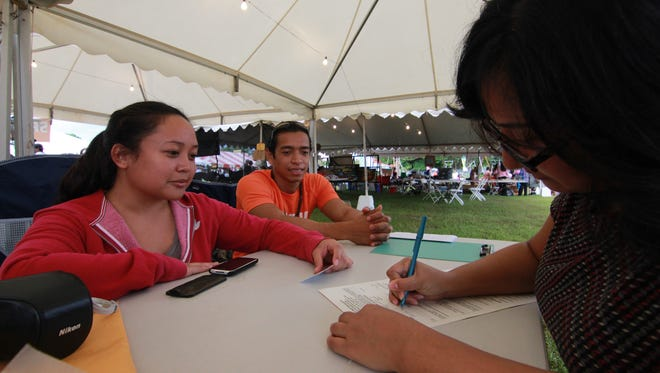 In this file photo, a voter signs up for the Decolonization Registry at the 2012 Micronesian Island Fair.