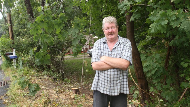John Shanley stands outside his Lake Carmel home where a contractor for NYSEG mistakenly cut down some of his trees Aug. 11, 2015.