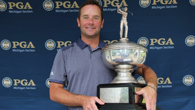 Dan Urban celebrates the Michigan PGA championship with the Gilbert A. Currie Trophy