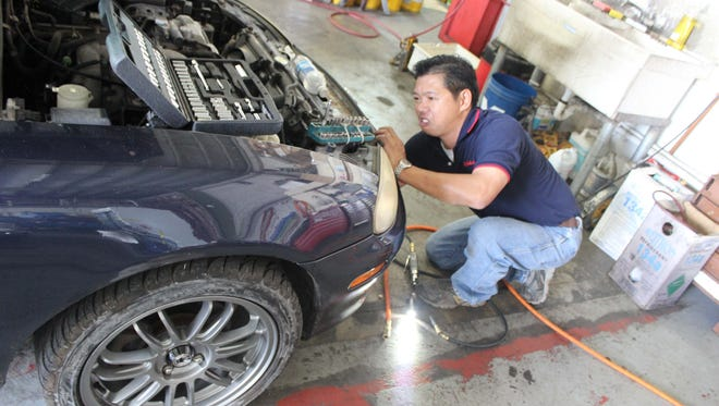 Kate Vongjalorn, manager at Comfort Auto Air Conditioning, prepares to tune up a vehicle's air-conditioning system at his shop in Harmon.