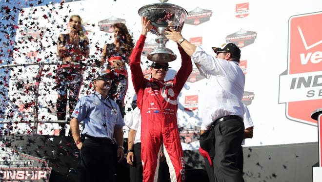 Aug. 30, 2015; Sonoma, Calif.; IndyCar Series driver Scott Dixon receives the trophy from team owner Chip Ganassi after winning the GoPro Grand Prix of Sonoma and the Verizon IndyCar Series championship at Sonoma Raceway.