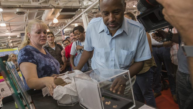 Republican presidential candidate Ben Carson looks at a display the Iowa Right for Life booth as he tours the Iowa State Fair in Des Moines, Ia., on Sunday, Aug. 16, 2015.