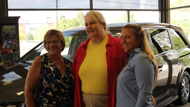 """East Brunswick Township Councilwoman Camille Clark, """"Mary"""" and Kim Branning of Branning Collision  Centers celebrate the donation of  the township mother's Recycled Ride."""