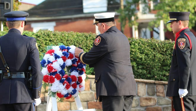 Clarksville Fire Chief Michael Roberts places a black flower on a memorial wreath Friday to honor the New York Fire Department personnel that died on Sept. 11, 2001.