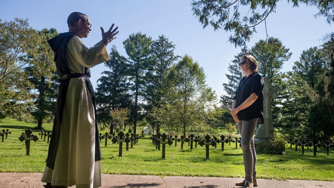Ames native Cassidy Hall tours the private cemetery where monks are laid to rest with Father Alberic Farbolin during a retreat at New Melleray Abbey in Peosta, Iowa, Wednesday, Sept. 9, 2015. Hall continues to communicate with Alberic and other monks she has encountered during her pilgrimage to all 17 Trappist monasteries in the United States inquiring monks and nuns about what silence means to them. Following that experience she joined a production team making the documentary film In Pursuit of Silence.