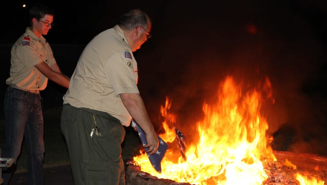 Dave Leavitt and a Boy Scout throw flags into the flames.