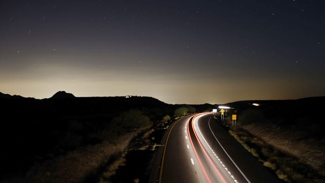 Taillights streak down Interstate 17 on a moonless night on Wednesday, Aug. 6, 2014 south of Black Canyon City, AZ. The southern horizon is illuminated with light from the metro Phoenix area. Photo by Rob Schumacher/The Arizona Republic