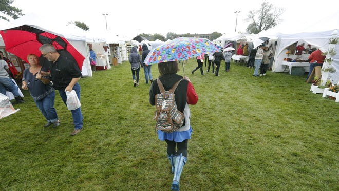 Dana Belles of Rochester walks through the rain at the Clothesline Festival at the M&T Bank Clothesline Festival at the Memorial Art Gallery on Saturday, Sept. 12, 2015.