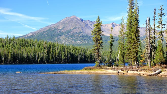 An island and the blue expanse of Summit Lake is seen below Diamond Peak in Deschutes National Forest.