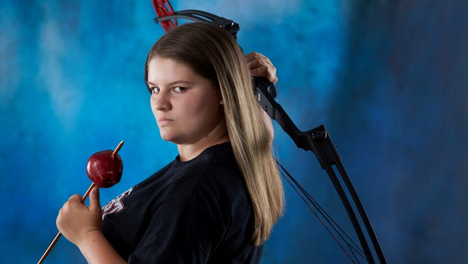 Paige Bootz poses for a senior portrait with a bow and arrow.