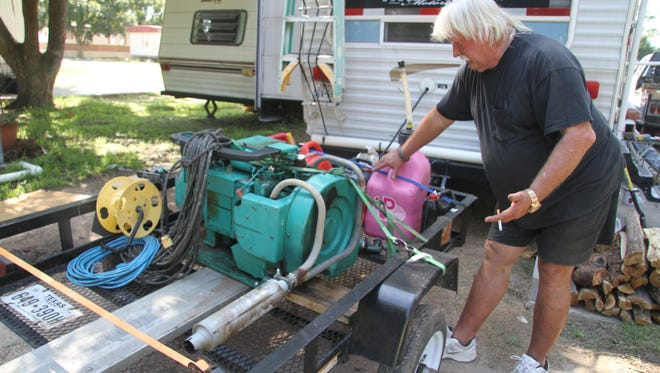 Gerald Prescott, a resident without power at Westwinds Mobile Home Park, explains his generator set-up outside his home on Wednesday.