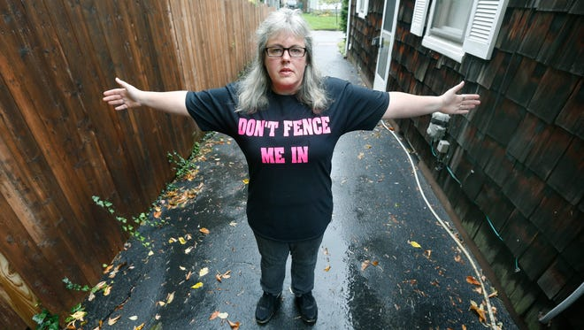 Tracy Hickmott's extends her arms in her driveway, which has been narrowed down by her neighbors whom she's in a dispute with over 1.8 feet of it. The neighbors have a survey that says they own 22 inches of land that Hickmott has been using as driveway since she moved there in 1999.