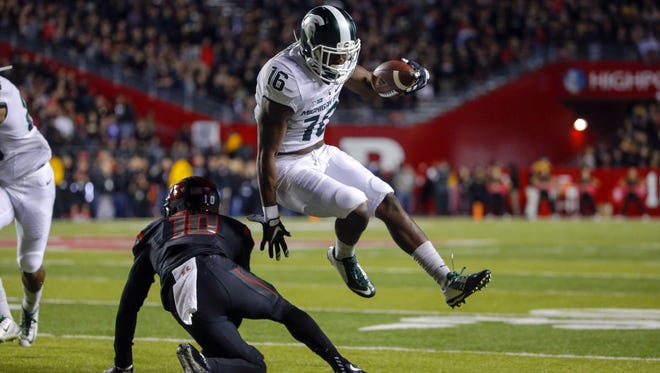 Michigan State's Aaron Burbridge (16) gets around Rutgers defensive back Blessuan Austin during the first quarter at High Points Solutions Stadium.