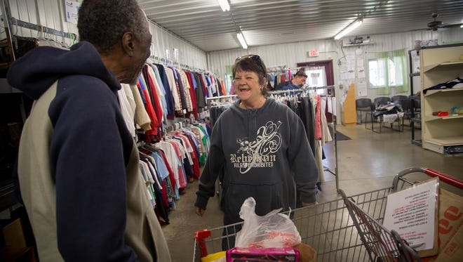 Bette McCaughey of Des Moines, laughs as food pantry employee John McDowell, left, tells her a joke as he helps her grocery shop at BidWell Riverside Center in Des Moines, Iowa, Monday, Oct. 12, 2015.