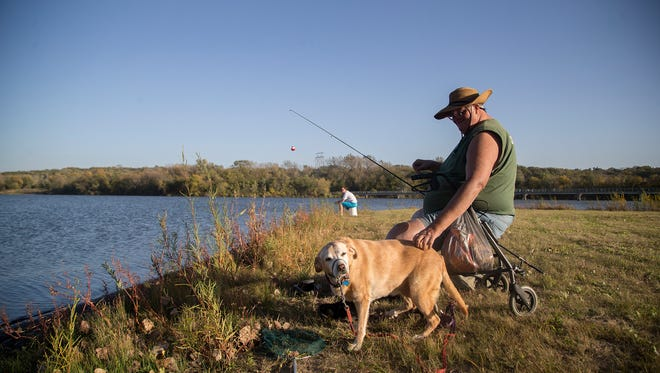 John Fischbach, of Lincoln, Neb., pets his dog, Angel, while fishing at Gray's Lake in Des Moines in 2015. The Iowa House has approved a bill that would allow unlicensed anglers to fish in ponds and lakes on private land.