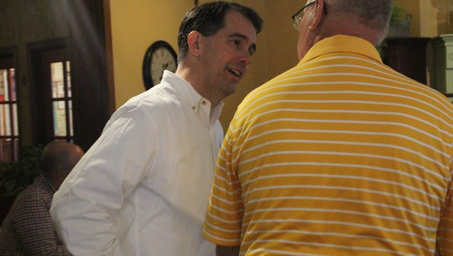Wisconsin Gov. Scott Walker (left) visits with a supporter during a stop Sunday, Sept. 20, at Serena's Cafe, Amana.