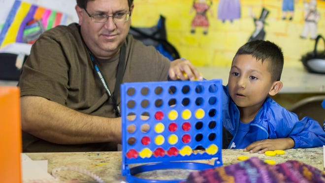Ezequial Alvarado, 6, right, plays Connect Four with Boys & Girls Club volunteer Ed Tsyitee. Volunteers serve as friends and role models to members of the Boys & Girls Club.