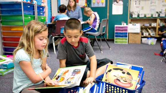Burk Elementary School students Cameron White and Rudy Ochoa read together on March 31, 2015.