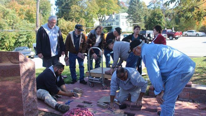 Purple Heart recipients and Cortlandt public works employees place memorial bricks at Purple Heart monument