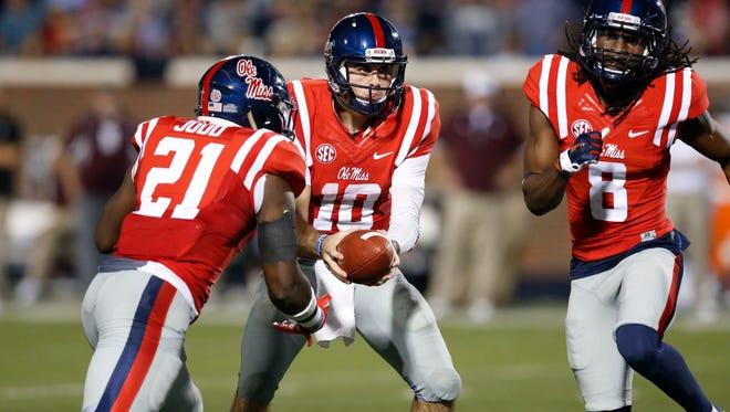 Ole Miss quarterback Chad Kelly prepares to hand off to running back Akeem Judd as wide receiver Quincy Adeboyejo runs a pattern during the second half against Texas A&M Saturday.