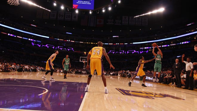 Former University of Rochester point guard John DiBartolomeo, far right, takes a jumpshot over Lakers guard Lou Williams as Kobe Bryant (24) looks on during an NBA exhibition game on Oct. 11. DiBartolomeo plays for a pro team from Israel.