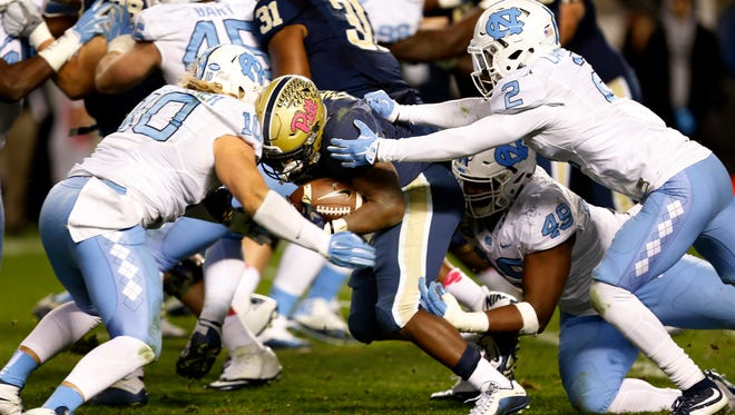 North Carolina linebacker Jeff Schoettmer (10) and cornerback Des Lawrence (2) stop Pittsburgh running back Chris James (5) on a run in the third quarter of an NCAA college football game, Thursday, Oct. 29, 2015, in Pittsburgh. North Carolina won 26-19.