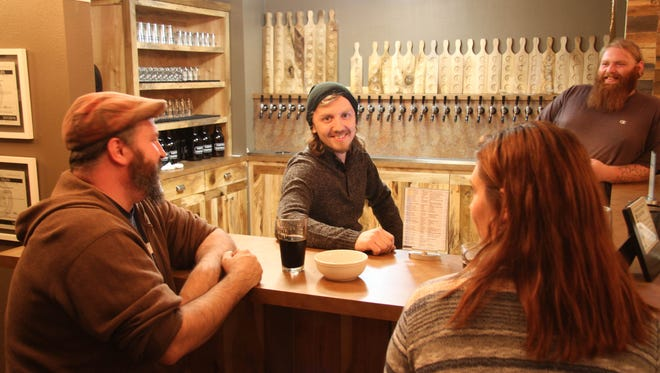Jon Shubin, center, owner of Capital Taproom, visits with patrons on Oct. 29.