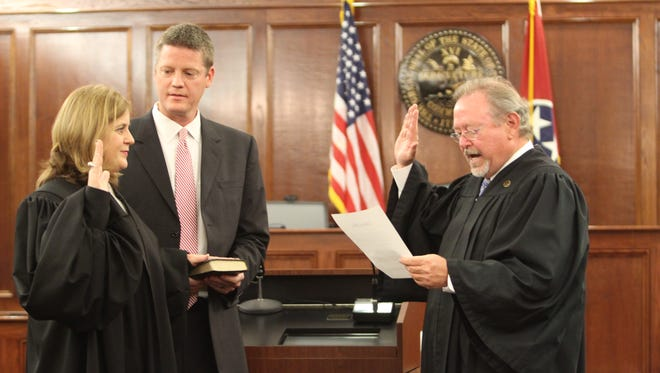 Jill Ayers puts one hand on a Bible held by her husband, Brian Ayers, as Judge Robert Wedemeyer leads her through the oath of office Friday.