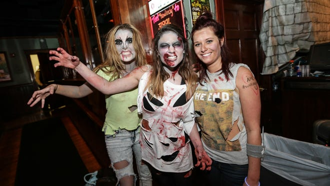 Left to right, Madleine Stone, Lindsey Fleming, Kendra Cannon, serve up drinks in costume for the Halloween Trolly Bar Crawl at Howl at the Moon, in downtown Indy.