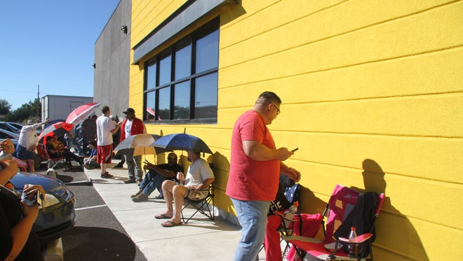 People tried to stay cool as they waited in line for the grand opening of Buffalo Wild Wings.