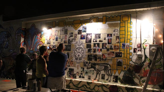 Participants paste pictures of their departed loved one on the remembrance wall at First City Art Center on North Guillemard Street Tuesday night as part of the Gonzalez St. Project.