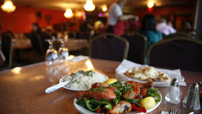 Chicken Tandoori, made with red and green bell peppers, onion and lemon, with rice and naan at Essence of India on Tuesday, Nov. 3, 2015.