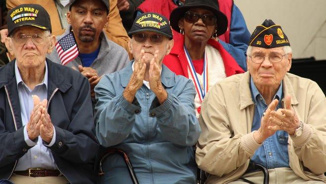 World  War II veterans Pete Edwards, left, Catesby Jones, center and Korean War era Marine Byrd Looper show their appreciation during Wednesday's Veterans Day ceremony at Memorial Stadium in Selma.
