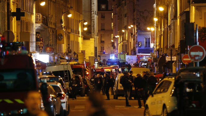 Police forces, firefighters and rescue workers secure the area near the Bataclan concert hall in central Paris, on Nov. 14, 2015.