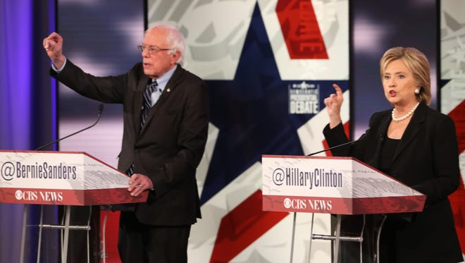 Bernie Sanders and Hillary Clinton talk over each other during Saturday's Democratic presidential debate at Drake University.