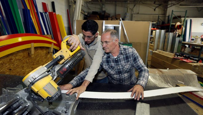 In a photo from Thursday, Oct. 8, 2015, in Warren, Mich., Albanian Mohamed Kaja, right, helps Syrian refugee Nidal Al-Haeuk with a mitre saw. Business owner Ismael Basha who came from Syria in the early 1980s, owns TSS Inc., which has 50 workers and makes automatic car wash fixtures and systems.
