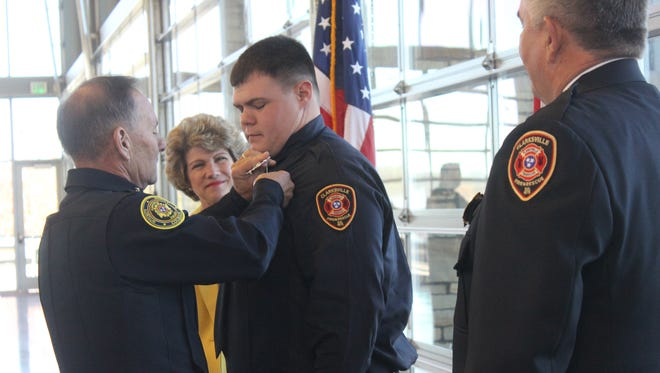 Clarksville Police Department Deputy Chief Frankie Gray pins a badge on new firefighter Jeff Welker as Clarksville Mayor Kim McMilland Fire Chief Michael Roberts look on.
