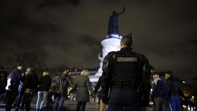Gendarmes stand by as people unite for a tribute near a makeshift memorial for the victims of a series of deadly attacks in Paris, at the Place de la Republique in Paris on Nov. 20, 2015.