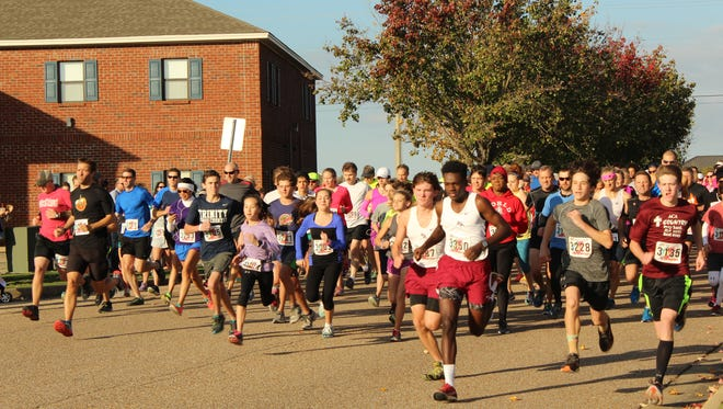 Hundreds of runners sprint from the starting line at the annual Montgomery MultiSport Turkey Burner event.