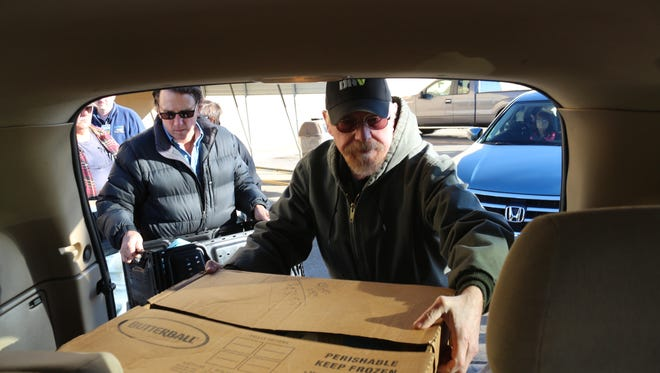 Veterans with the Disabled American Veterans, chapter 101, load cars with Thanksgiving meals Monday outside Wal-Mart in preparation to deliver the meals around town.