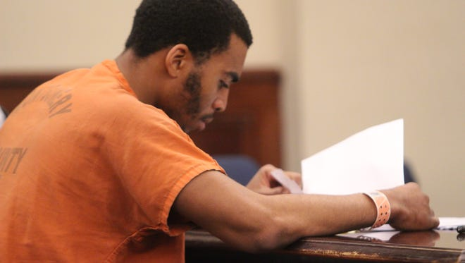 Zackery Alexander looks through papers at his preliminary hearing Tuesday.