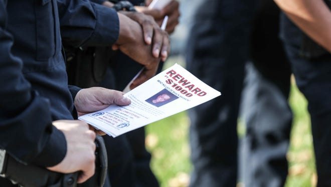 IMPD officers met for roll call Nov. 25, 2015, outside the house in the 3900 block of Graceland Avenue where Deshaun Swanson, 10, was gunned down while attending a memorial service Sept. 19. Police posted fliers around the community seeking help in solving the case.