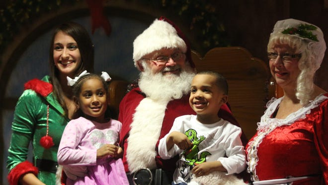 Two kids sit on Santa's lap Tuesday at Fort Campbell as the post held its annual tree lighting ceremony at Division Headquarters.