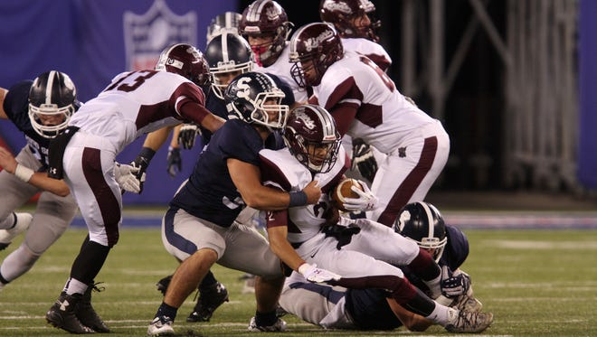 Middletown South's Dylan Rogers tackles Phillipsburg's Jaquan Jones in the first quarter during the North 2 Group IV championship game at  MetLife Stadium in East Rutherford, NJ Saturday December 5, 2015.