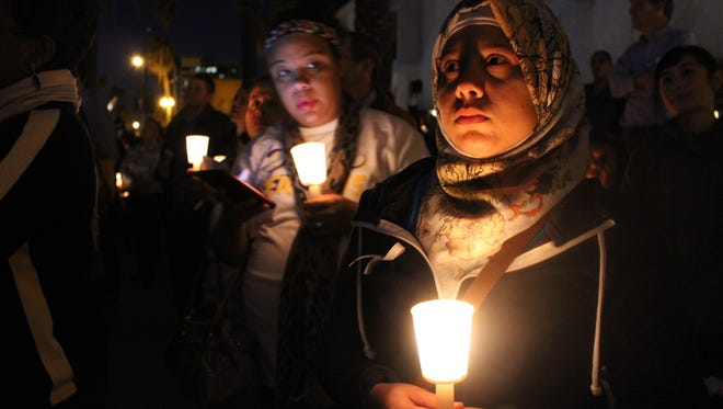 Shenaz Makati, a 28-year-old Muslim woman who works at the San Bernardino library, holds a lit candle during a prayer vigil in the city on Monday, Dec. 7.